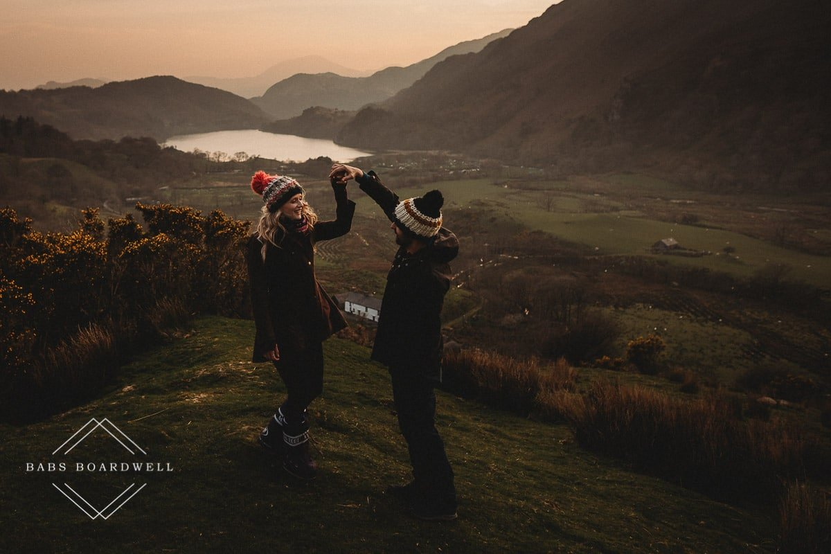 couple twirling in hand wearing knitted bobble hats and moon boots at sunset with a lake and mountains in the background