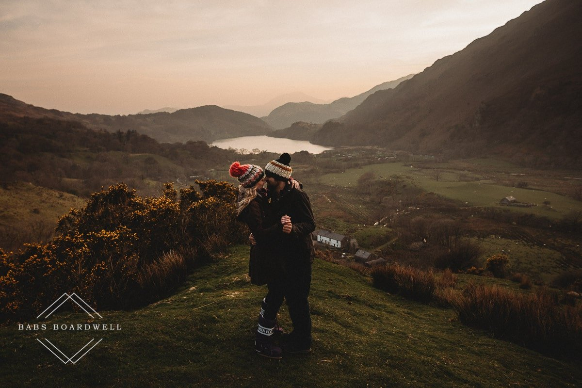 couple silent dancing wearing knitted bobble hats and moon boots at sunset with a lake and mountains in the background