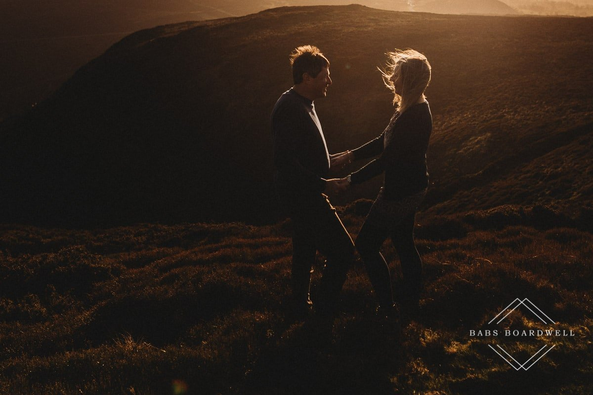 couple holding hands standing opposite one another and looking at each other at sunset