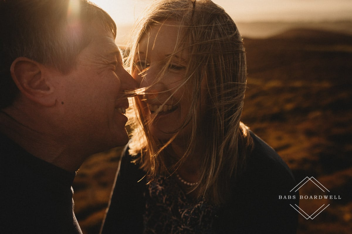 couple at sunset looking at each other and laughing