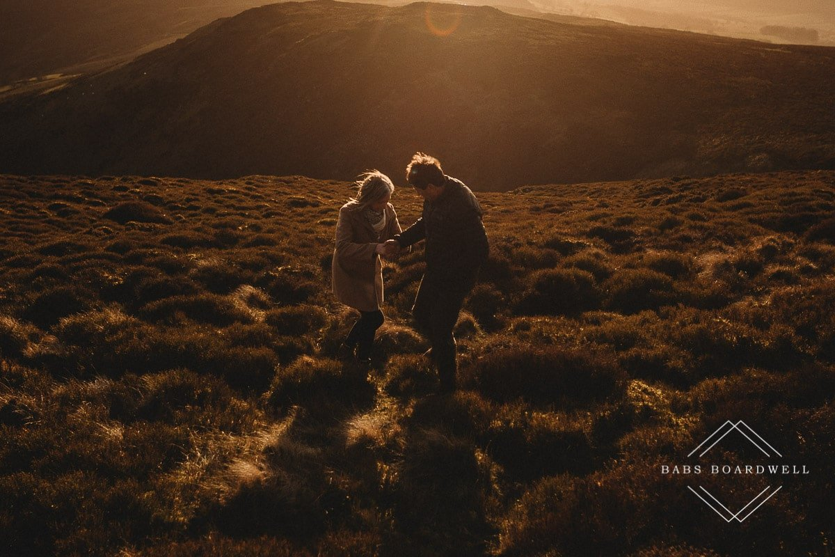 couple at sunset walking across the heather in North Wales
