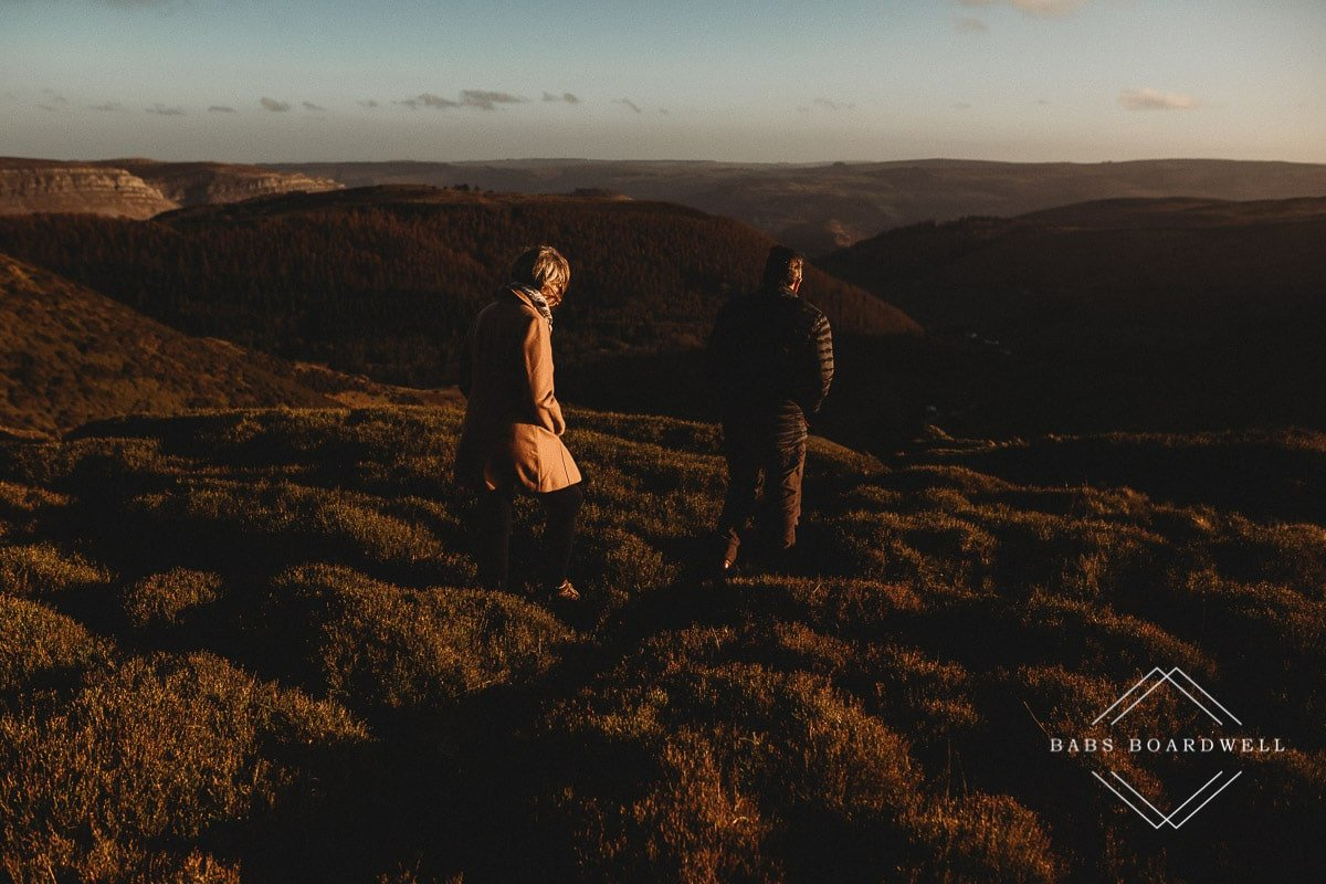 couple walking across the heather overlooking World's End in Llangollen at sunset