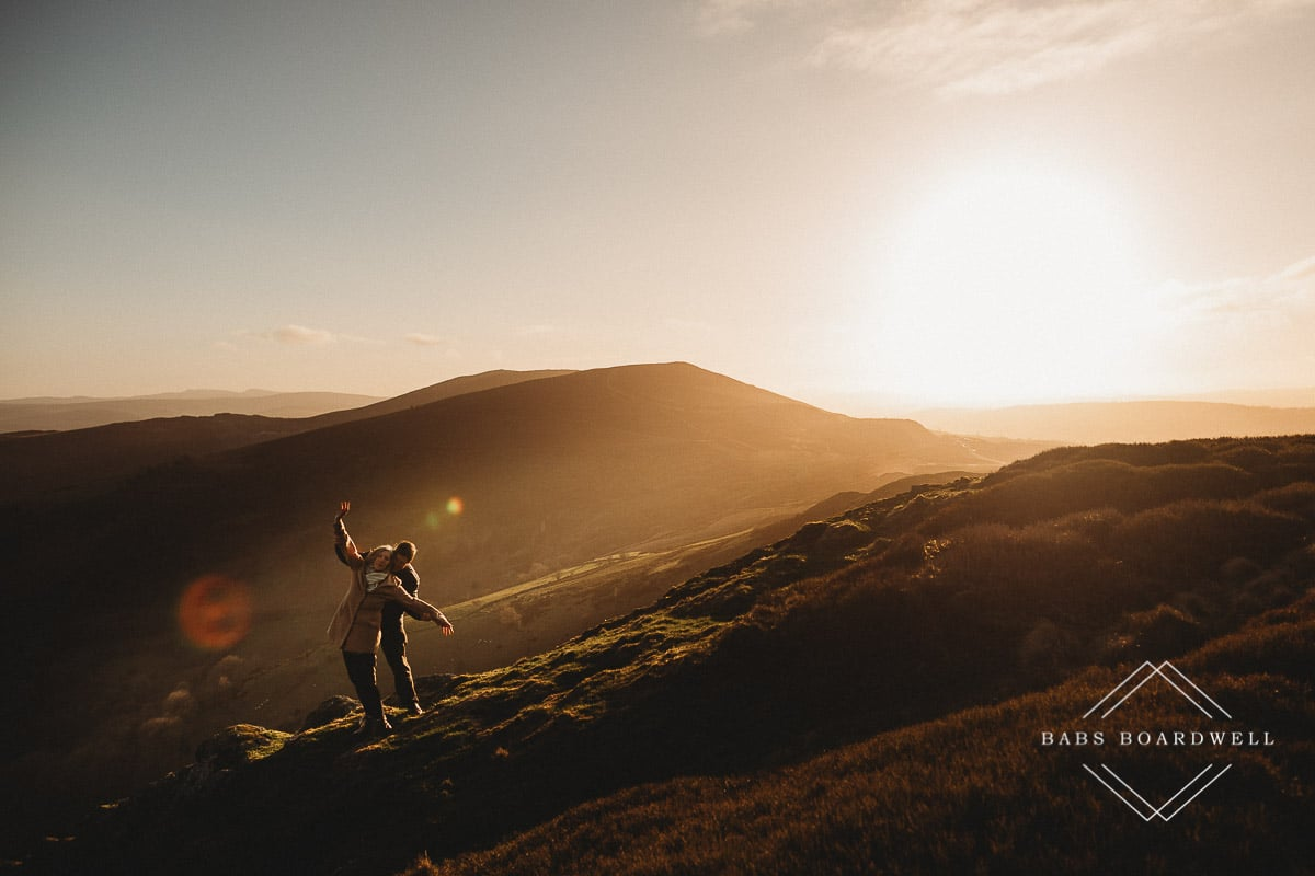couple pretending to be on the Titanic in the hills in North Wales at sunset