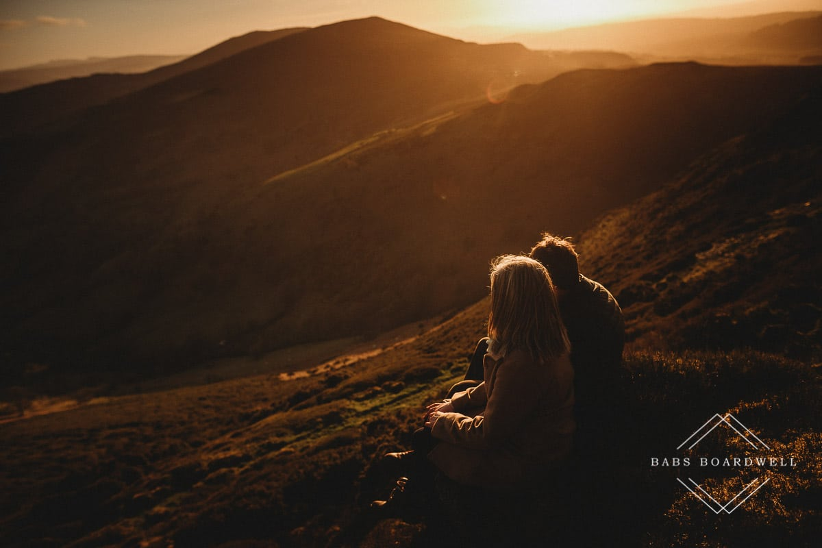 couple sitting next to each other overlooking Welsh scenery at sunset