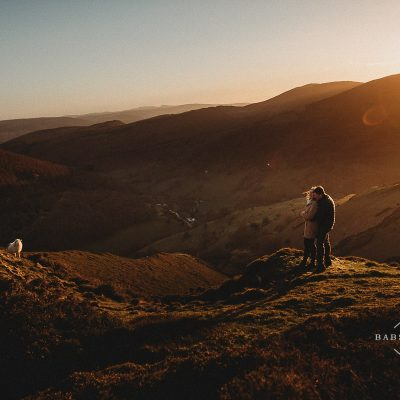 couple hugging at sunset in North Wales with a sheep walking into the frame