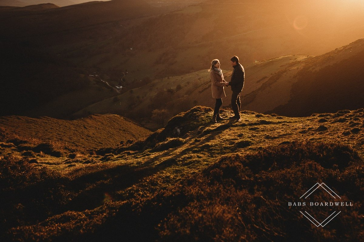 couple holding hands in the hills at sunset by Denbigh Wedding Photographer