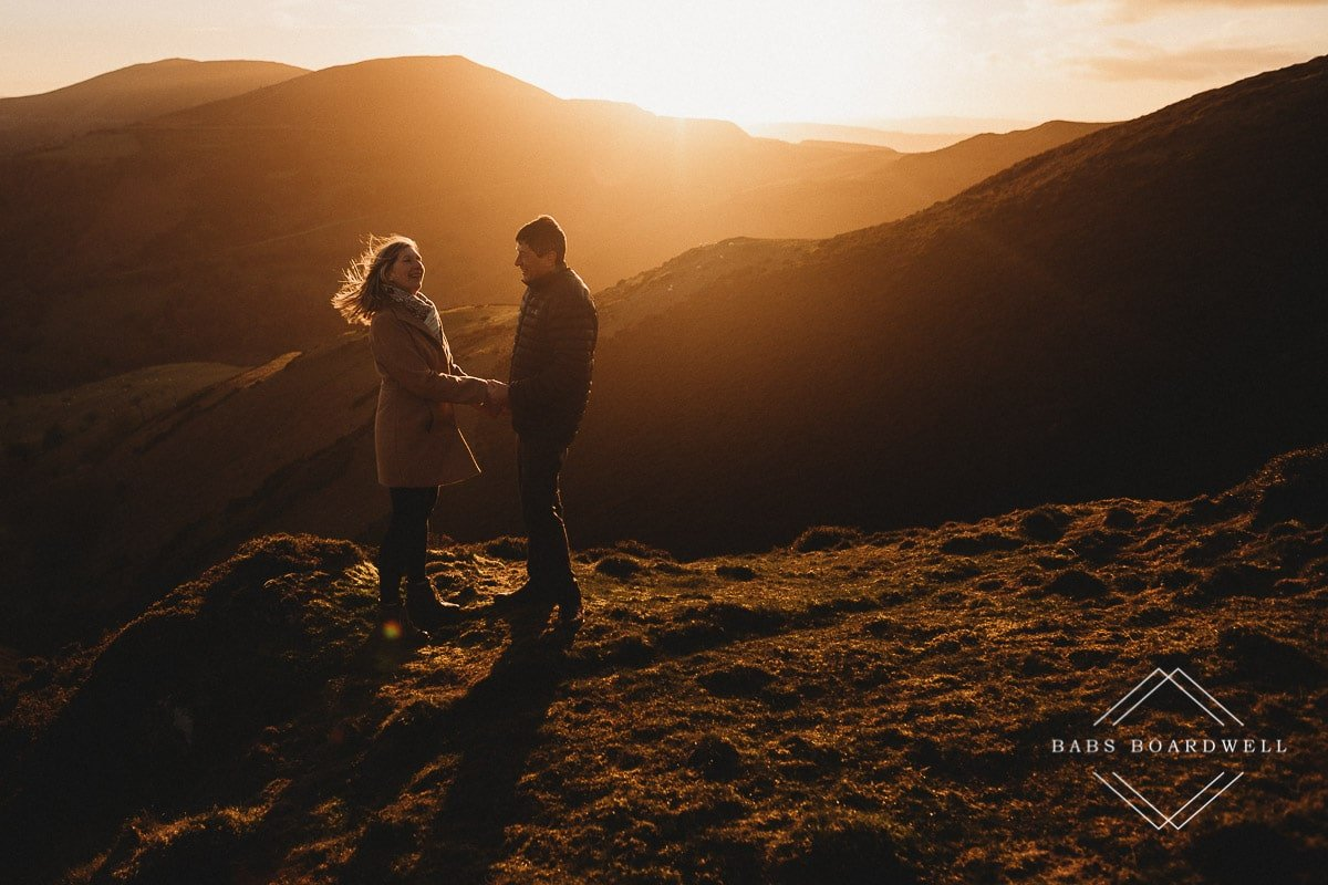 couple holding hands at sunset with the woman's hair blowing in the wind