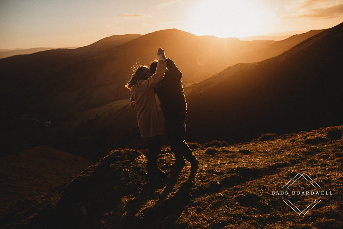 couple pretending to dance at sunset in the Welsh hills