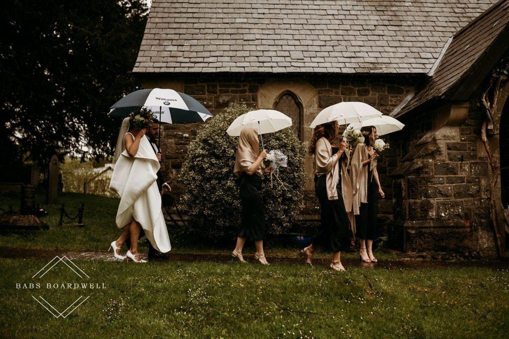bridal party and bride walking to church in the rain holding umbrellas for a beautiful wedding at the Gwenfrewi Project