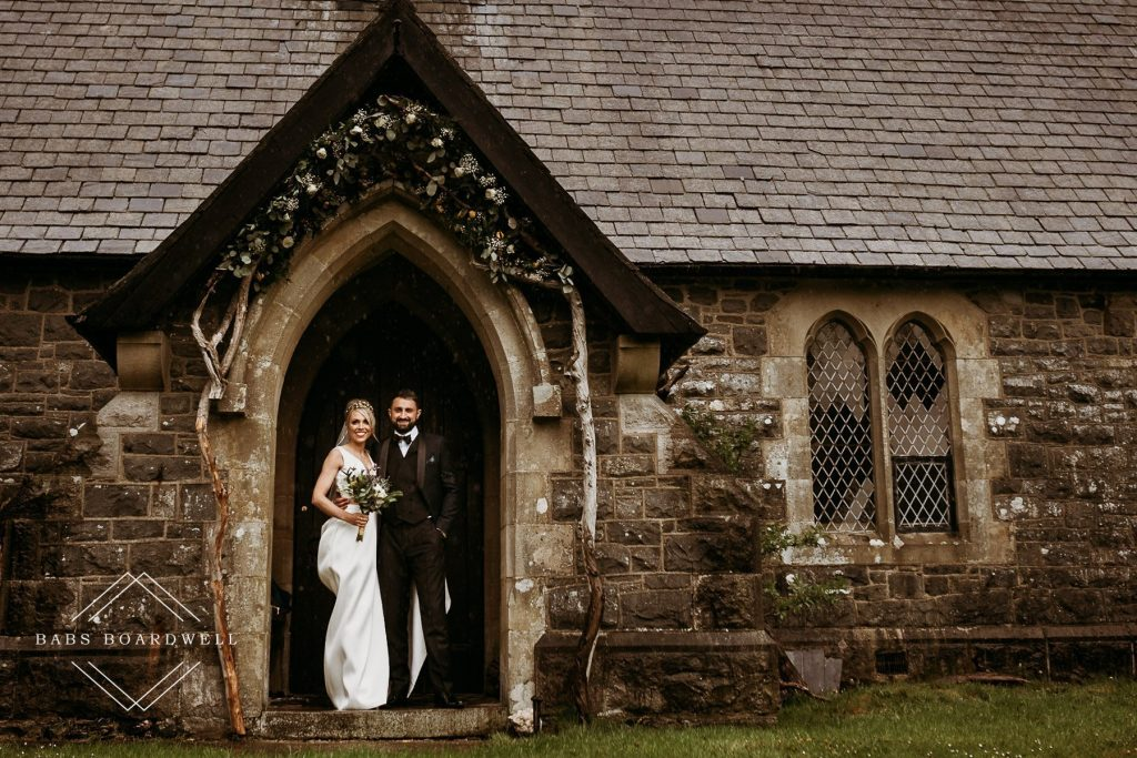 bride and groom posing outside the venue after a beautiful wedding at the Gwenfrewi Project