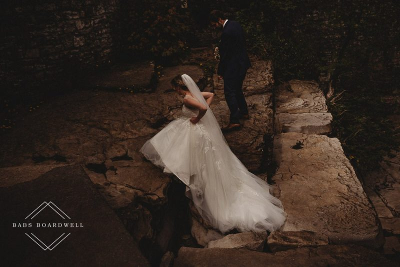 bride hitching her dress up walking up on some rocks while her groom looks on