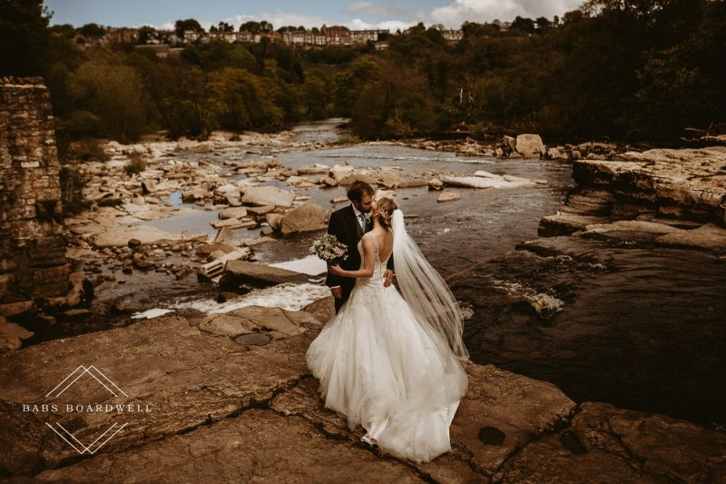 Newly married couple getting married at Low Gingerfield Farm kissing overlooking the falls in Richmond North Yorkshire