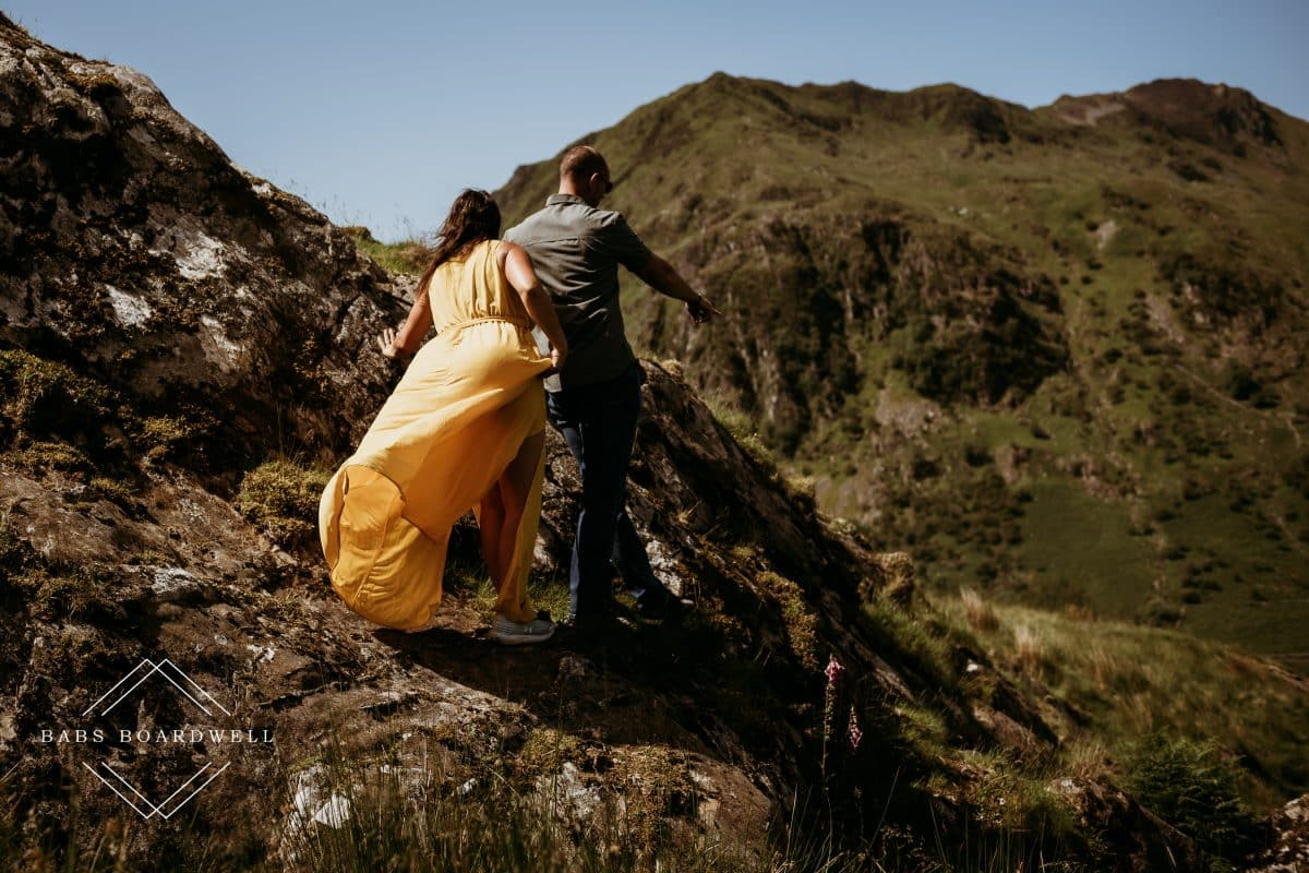 bride in yellow dress being led across rocky mountains by casual groom