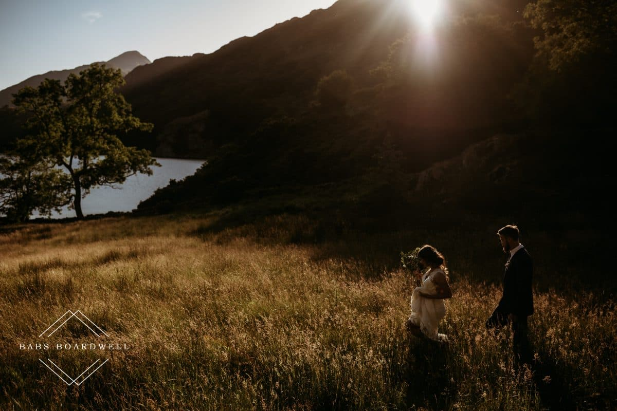 bride and groom walking in a field towards Llyn Gwynant at sunset