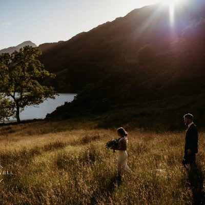 bride and groom walking across a field against the backdrop of Llyn Gwynant at sunset