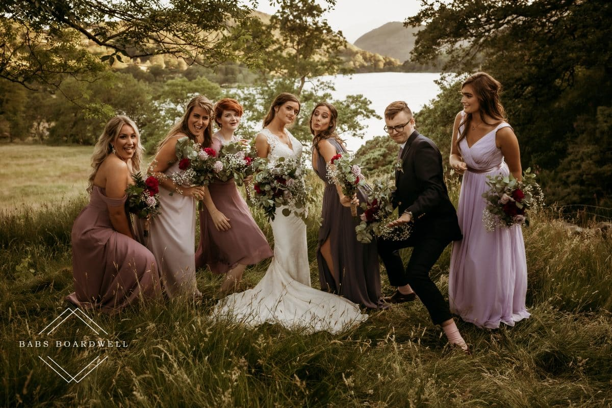 group picture of bridesmaids in blush pink dresses and bride in a white wedding dress holding bouquets pretending to dance against the backdrop of Llyn Gwynant