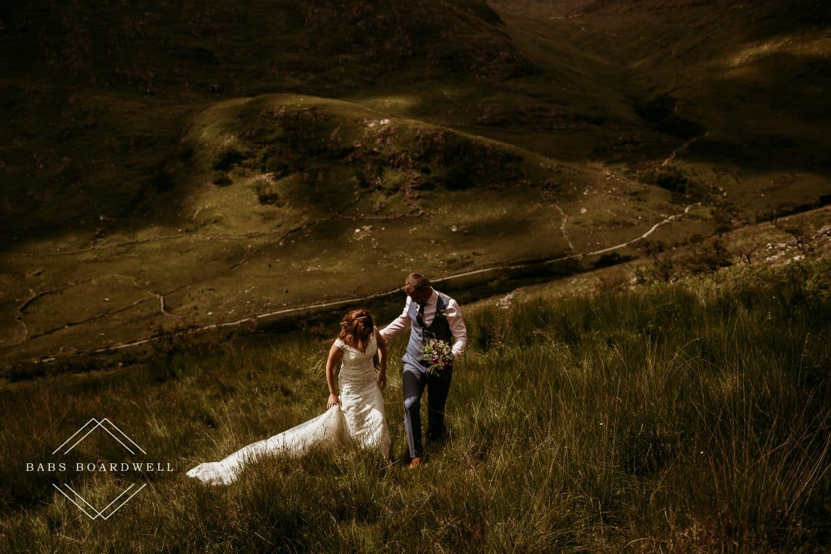 bride and groom walking uphill with groom holding the bride's bouquet against a mountain backdrop
