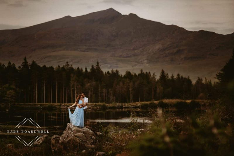bride and groom on a tree stump in front of Snowdon with a lake in the background