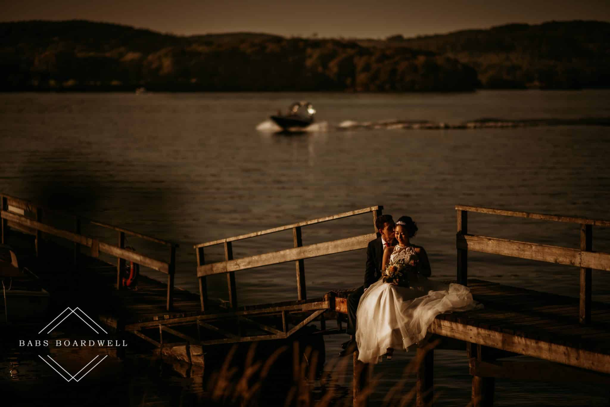 bride and groom sitting on a jetty on Windermere looking at each other at sunset with a speedboat in the background