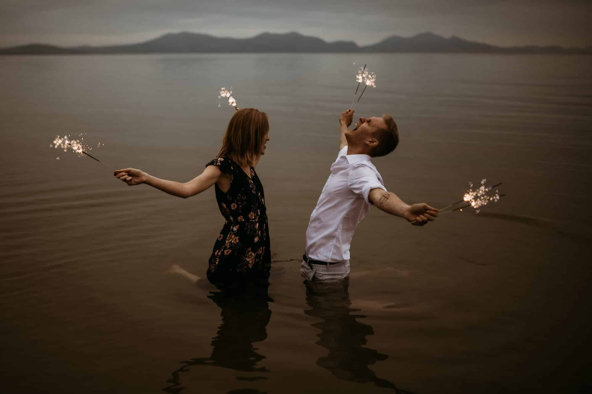 couple in the sea with mountains in the background playing around with lit sparklers