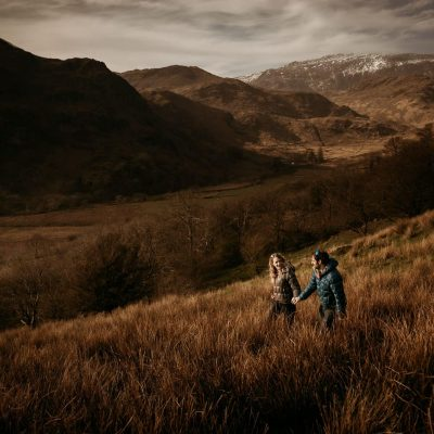 couple holding hands walking across a path in Snowdonia with snowcapped mountains in the background