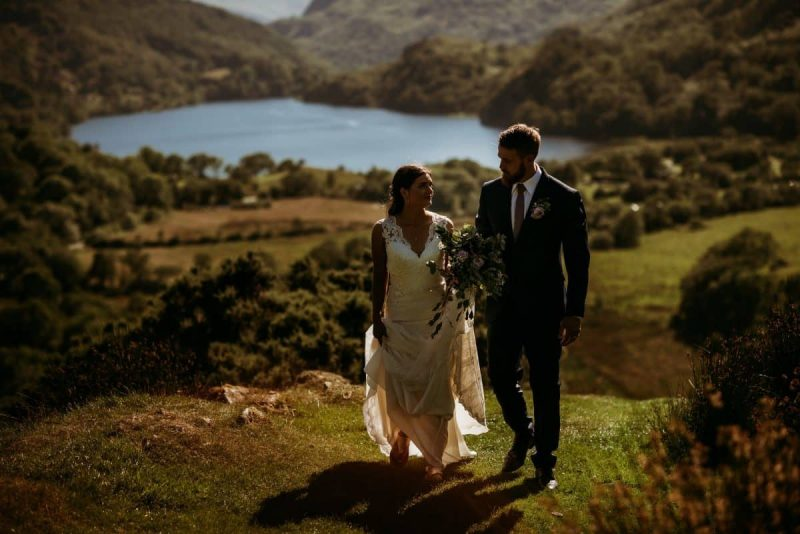 bride and groom walking side by side with Llyn Gwynant in the valley behind them