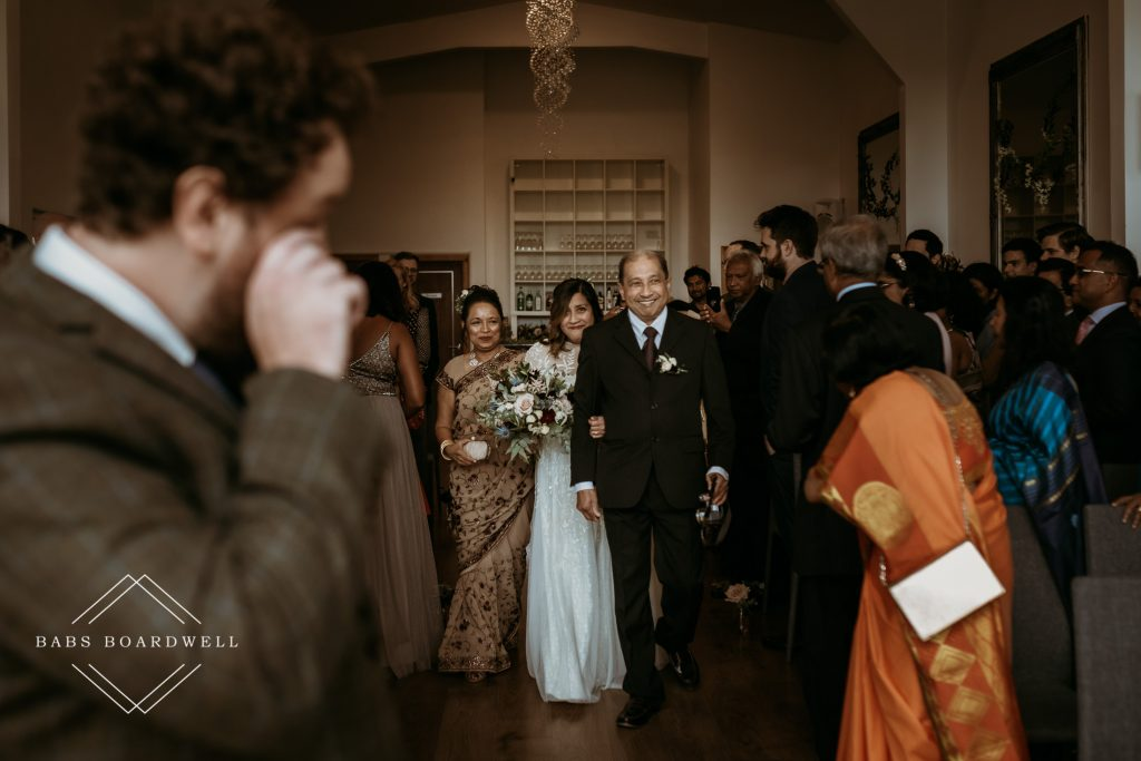bride walking down the aisle on the arms of her mother and father with the groom wiping away a tear from his eye waiting at the end of the aisle during this English Sri Lankan fusion wedding at Holmfirth Vineyard
