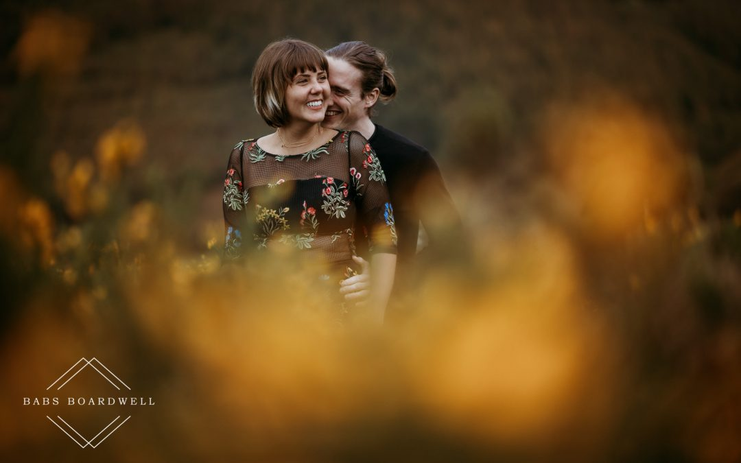 couple hugging in yellow gorse during their Llangollen Engagement Session