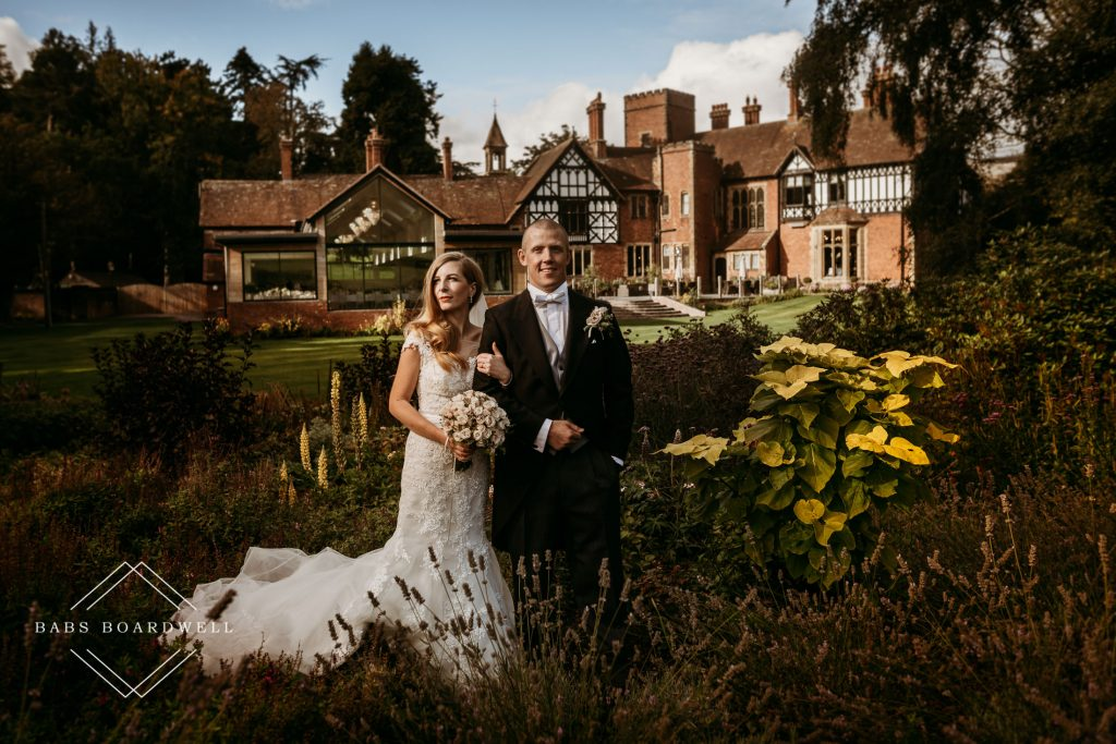 bride and groom posing in the gardens at Tyn Dwr Hall