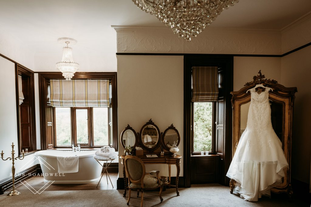 wedding dress hung on a wardrobe in one of the bedrooms during a romantic wedding at Tyn Dwr Hall