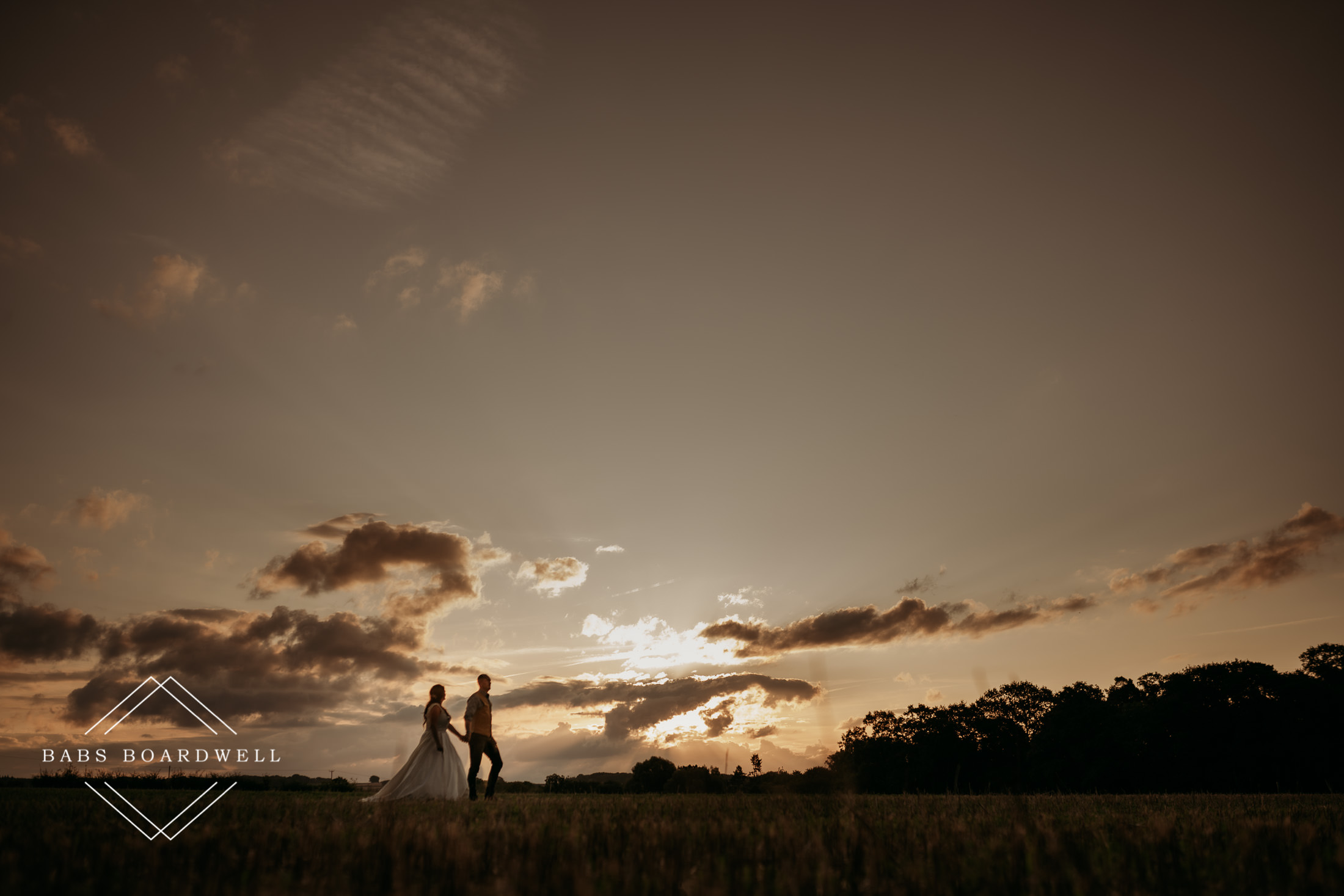 bride and groom walking across a field holding hands at sunset by North Wales Wedding Photographer