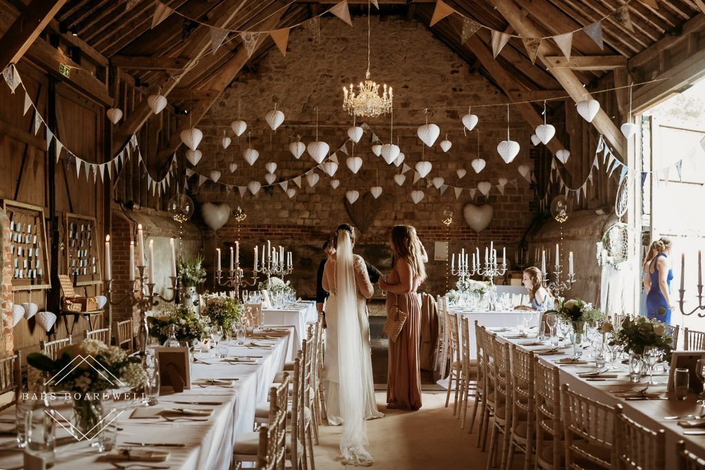 bride with her back to the camera chatting to her bridesmaids inside a wedding barn by North Wales Wedding Photographer