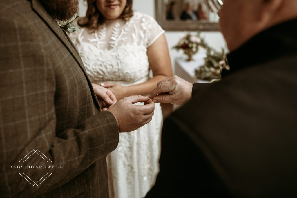 close-up of groom taking ring from his father