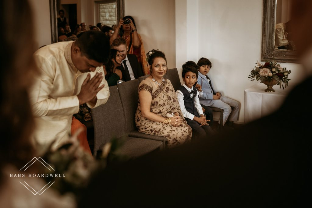 Holy man bowing with mother of the bride and some children looking on