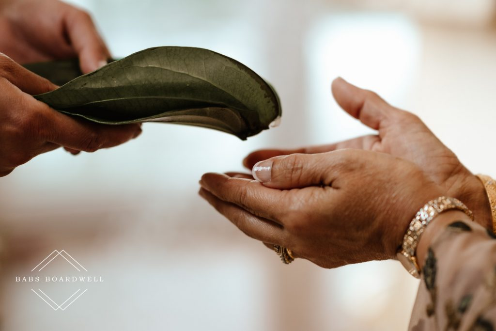close-up of leaves being handed to a pair of female hands during Sri Lankan Wedding Ceremony at Holmfirth Vineyard