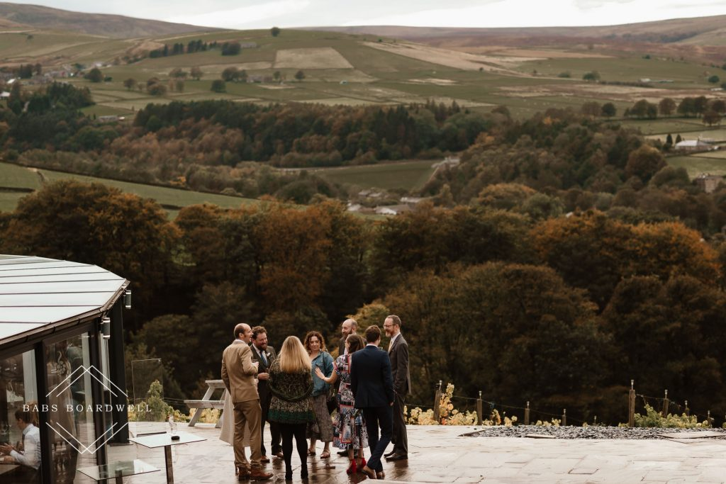 wedding guests on the outside terrace at Holmfirth Vineyard