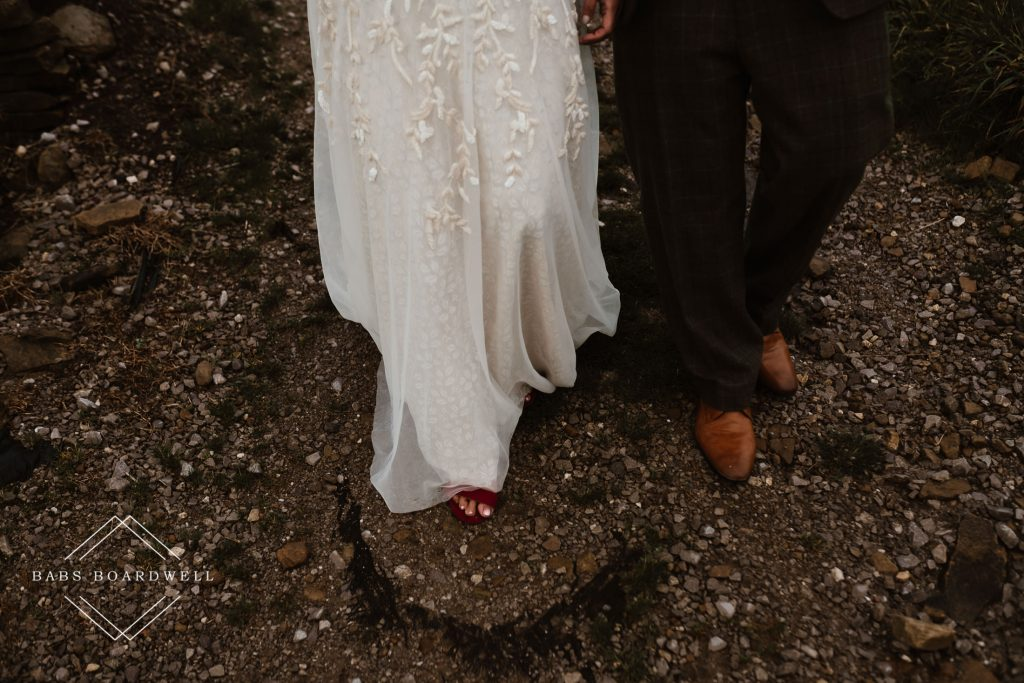 close-up of bride and grooms lower legs, wedding dress and shoes