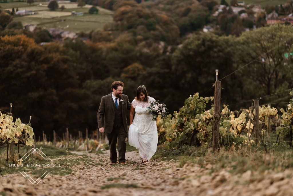 bride and groom walking up towards the building from the vineyard at Holmfirth Vineyard