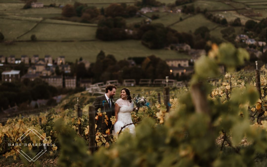 bride and groom walking while looking at each other at Holmfirth Vineyard