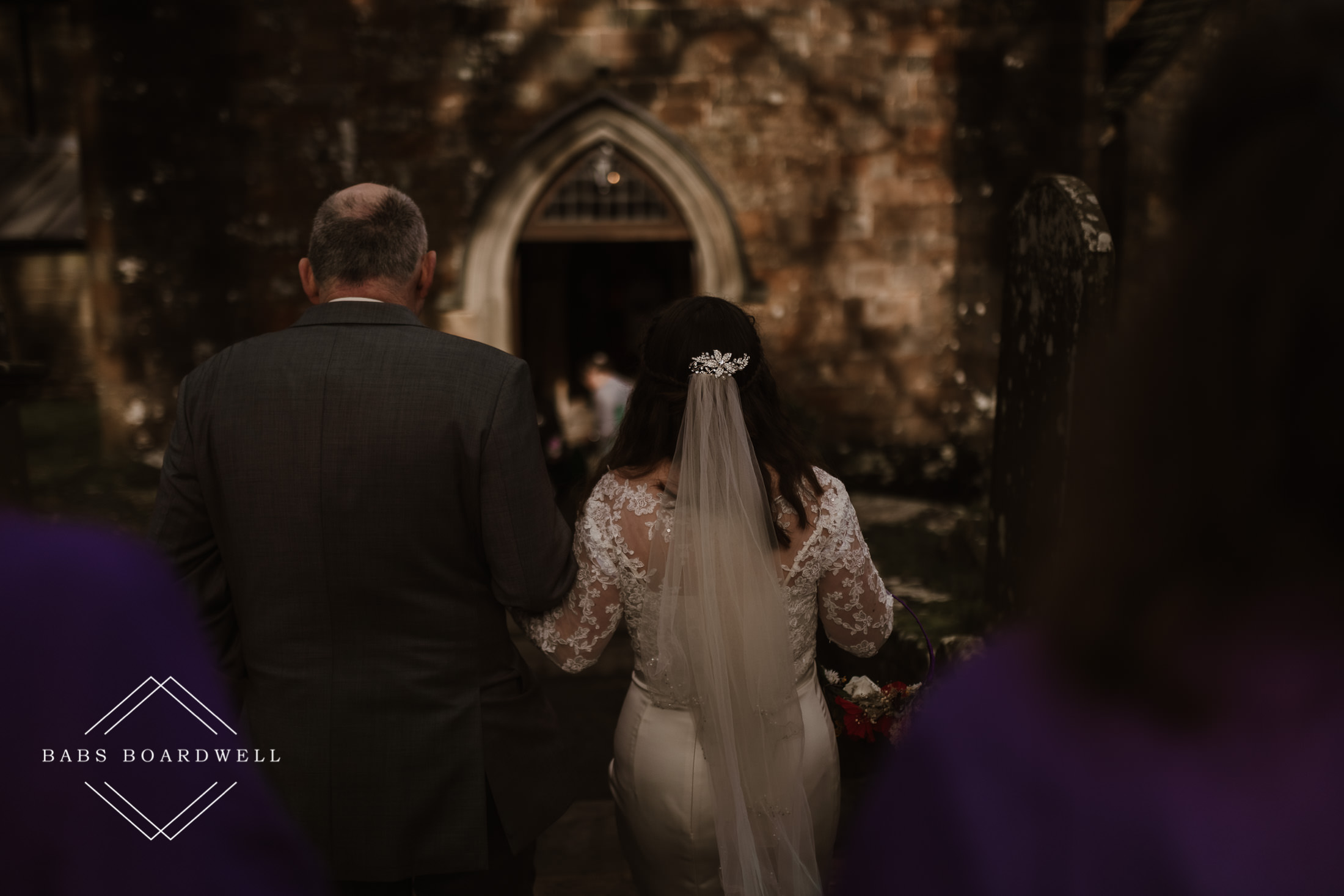 bride being walked into church on the arm of her father at St. Briavels Church
