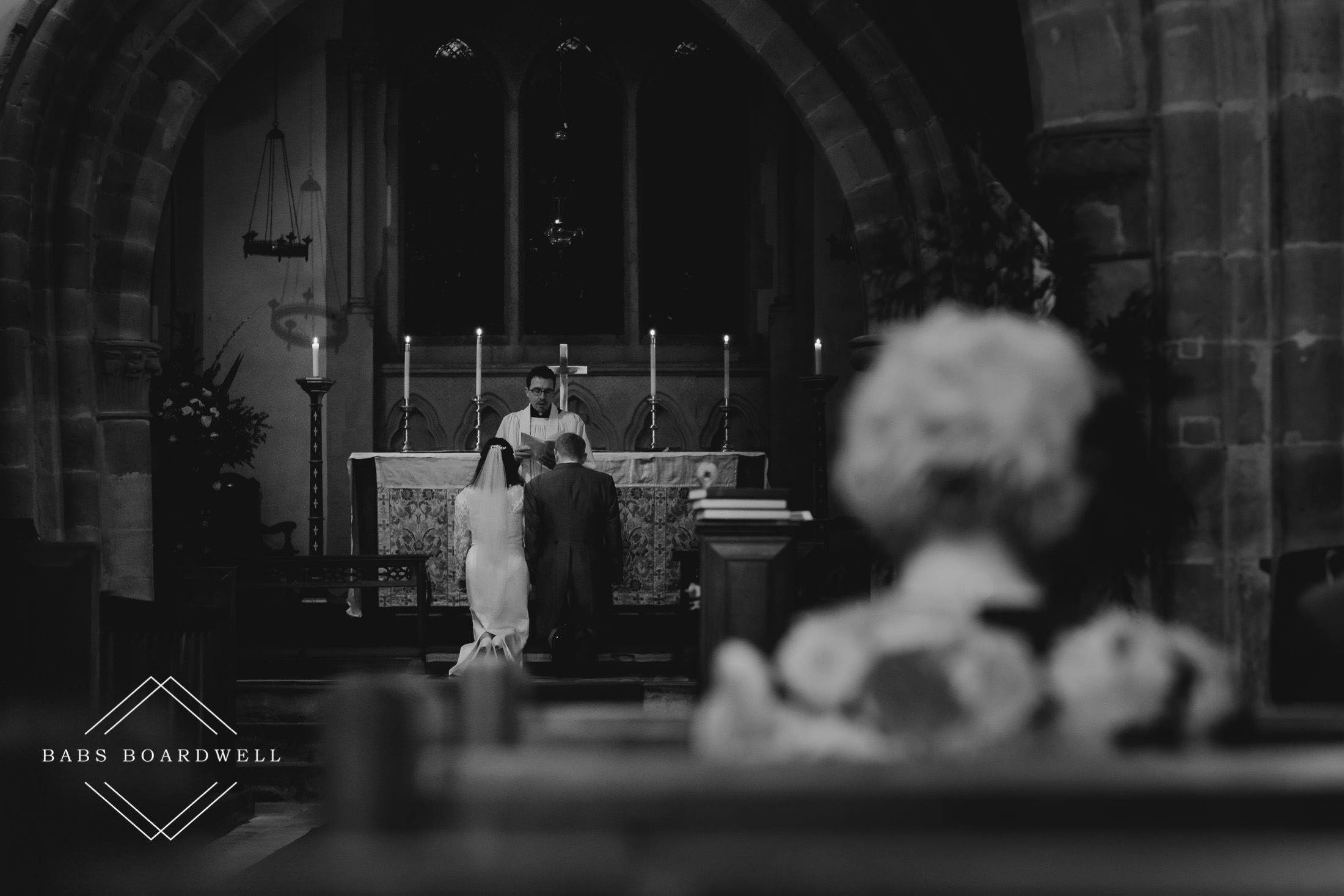 black and white image of the bride and groom kneeling in the holy chamber during wedding ceremony at St Briavels chapel