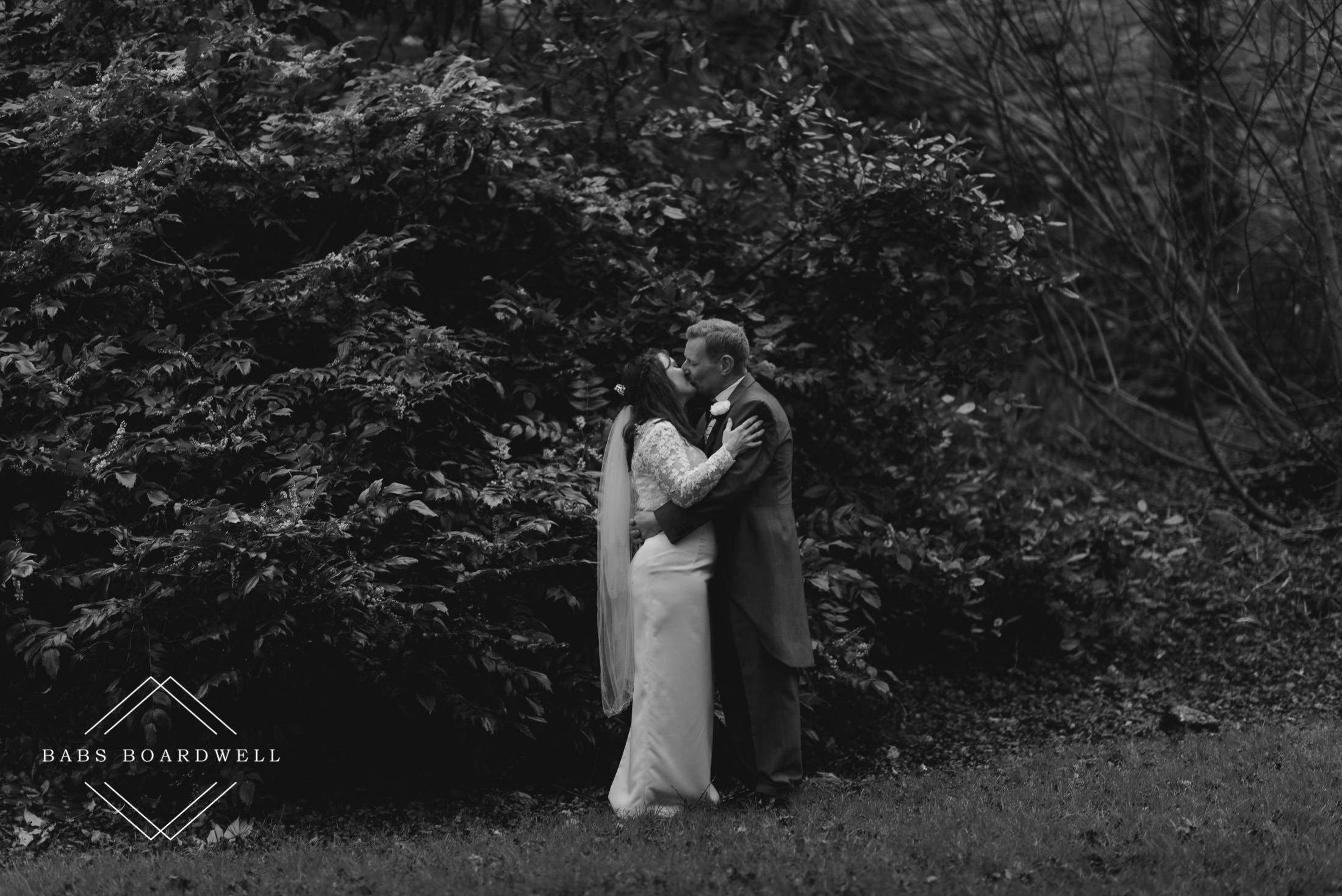 black and white portrait of bride and groom hugging and kissing at St Briavels Castle