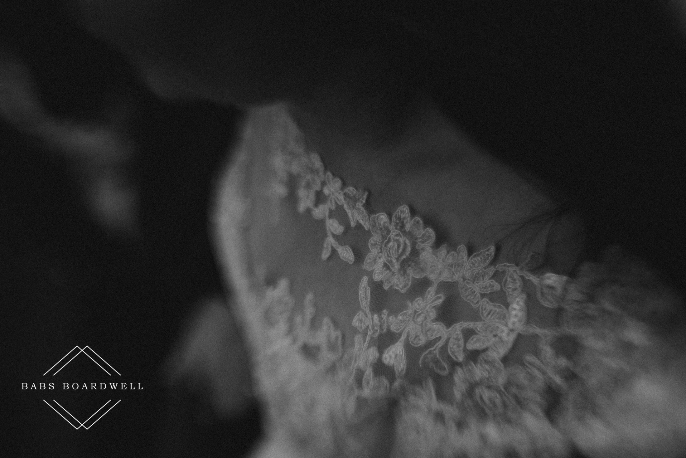 close-up of black and white image of details on bride's dress