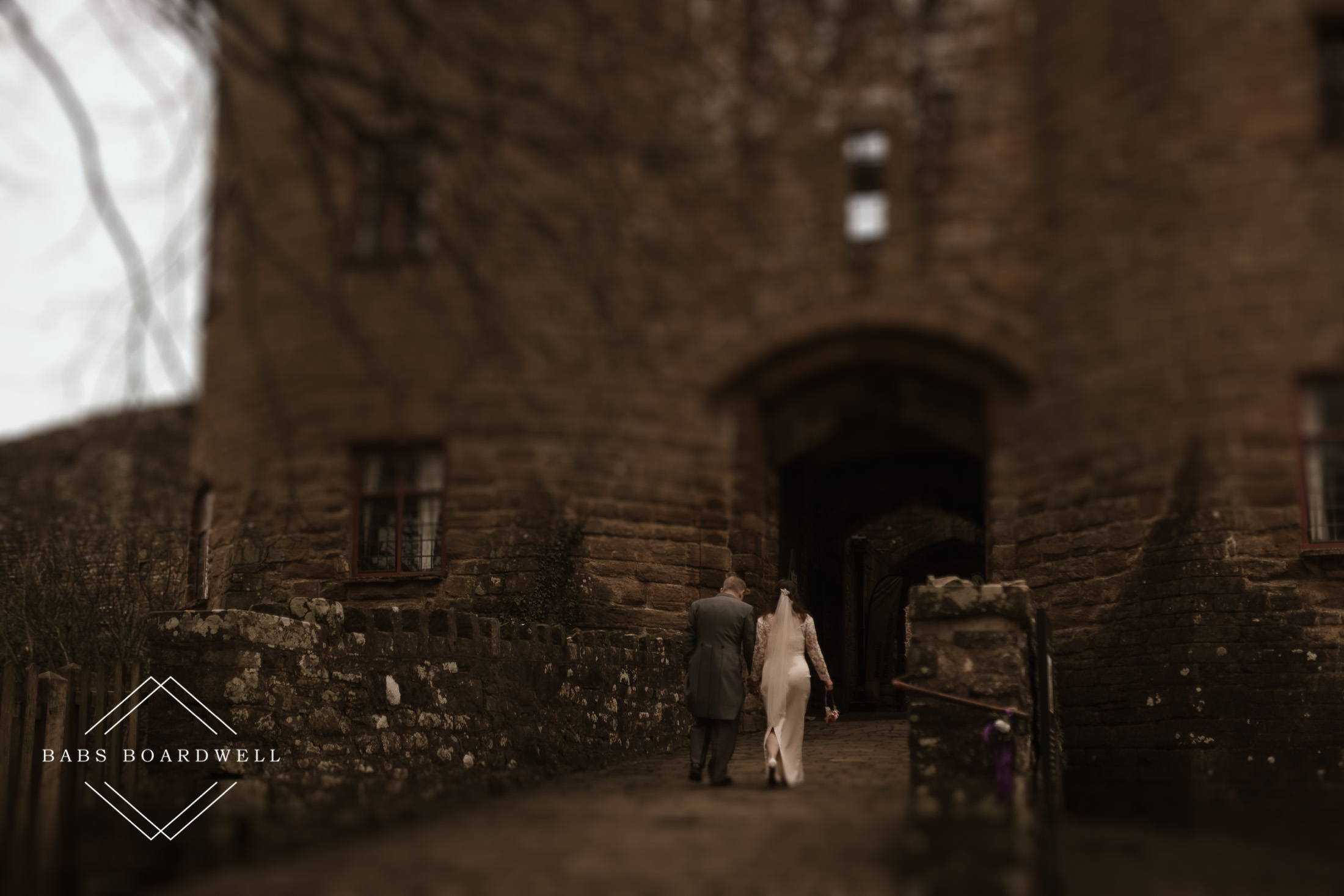 bride and groom walking towards the gate on their wedding day at St Briavels Castle
