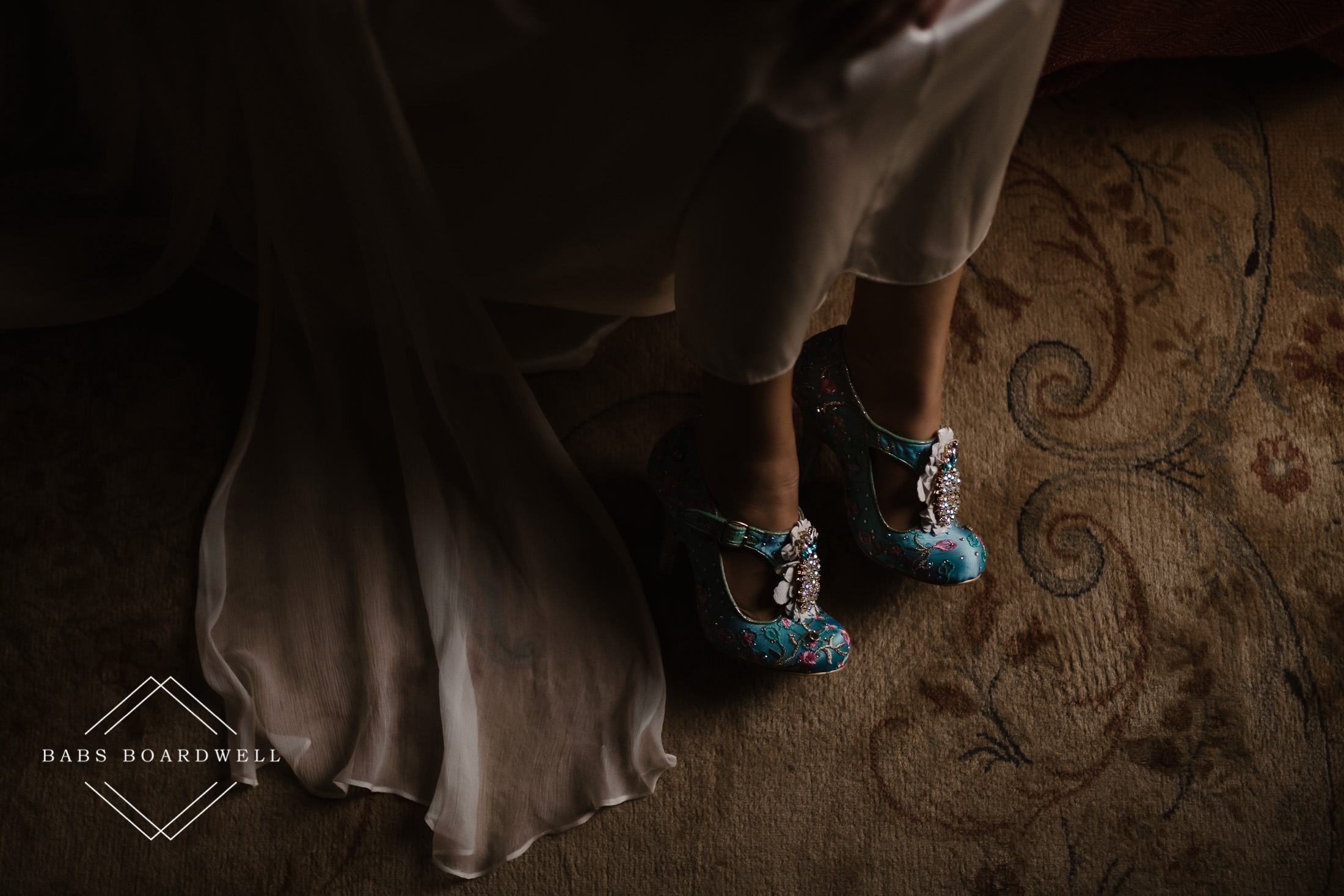 close up of bride's blue wedding shoes next to her veil