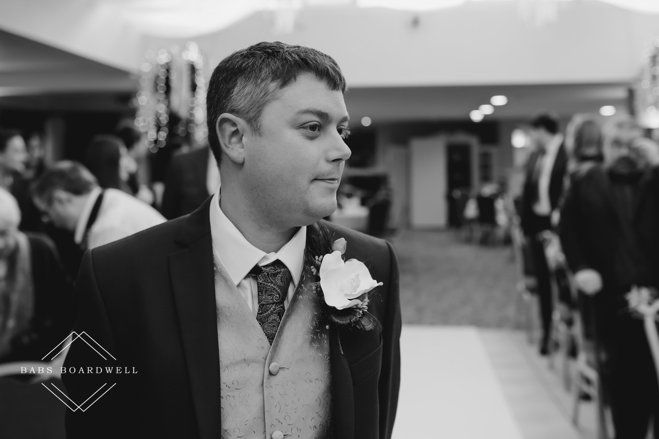 black and white image of groom waiting for his bride to walk down the aisle