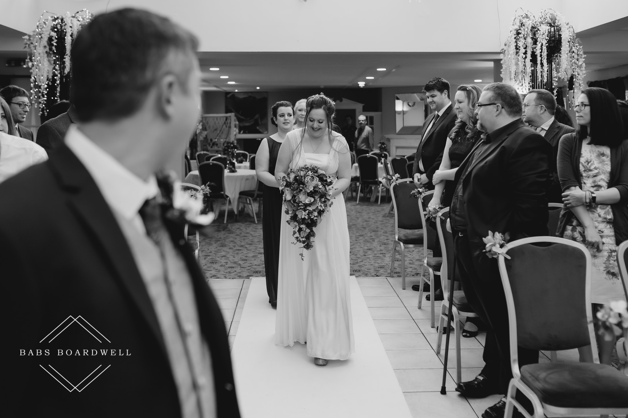 black and white image of groom looking in the direction of his bride walking down the aisle