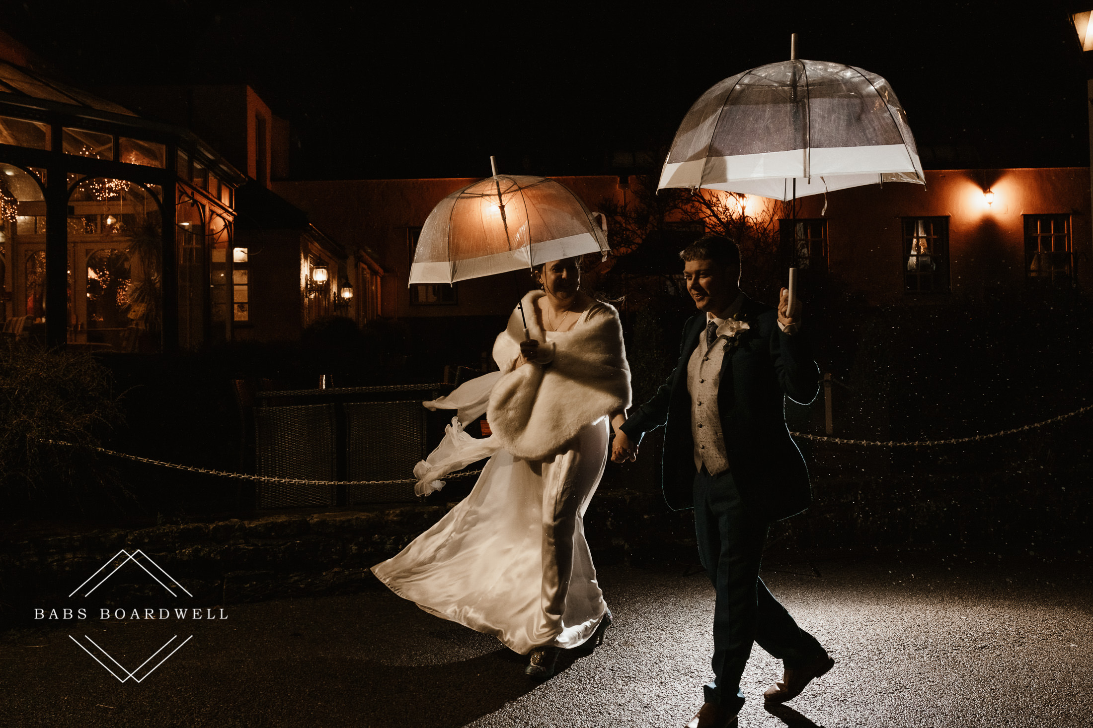 bride and groom walking at night with umbrellas in the rain during spring wedding at Plas Hafod Country House Hotel