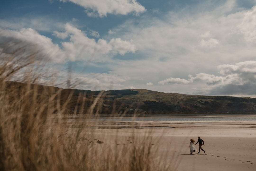couple walking hand in hand along Barmouth Beach by North Wales Wedding & Elopement Photographer