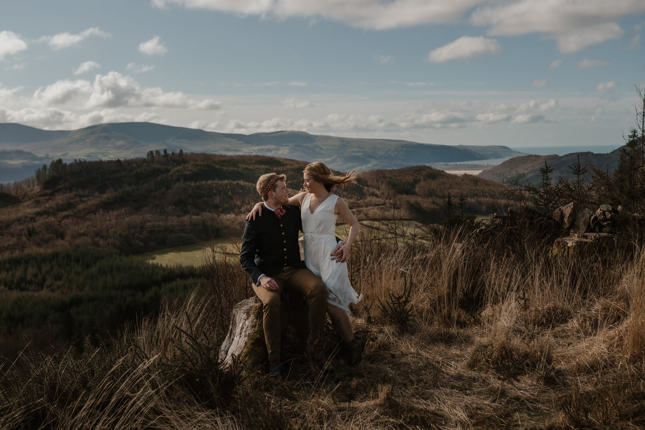 bride and groom on their Snowdonia Elopement day hugging on a tree stump above Barmouth by North Wales Wedding Photographer